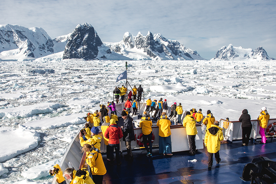 Passengers stand at the hull of the ship as they cruise through sea ice