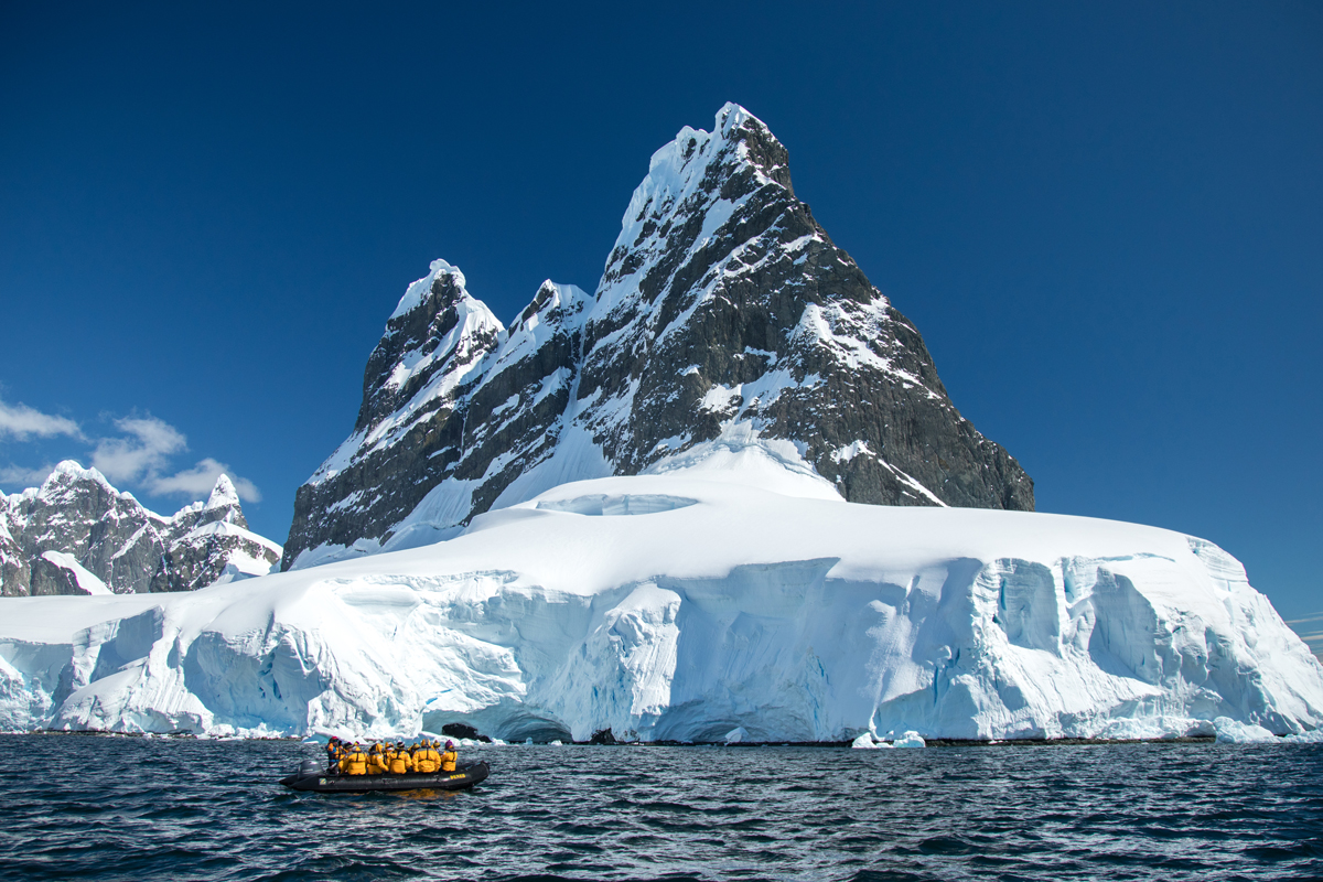 Passengers Zodiac cruise through the Lemaire Channel, in the Antarctic Peninsula