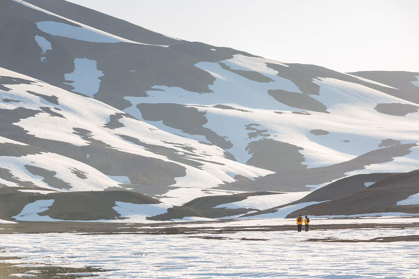 A couple pictured hiking in Dream Bay, East Greenland. Photo by Acacia Johnson