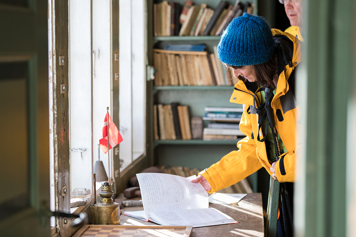 Quark Expeditions passenger reviews the log of visitors who have passed through over time. Photo: Acacia Johnson
