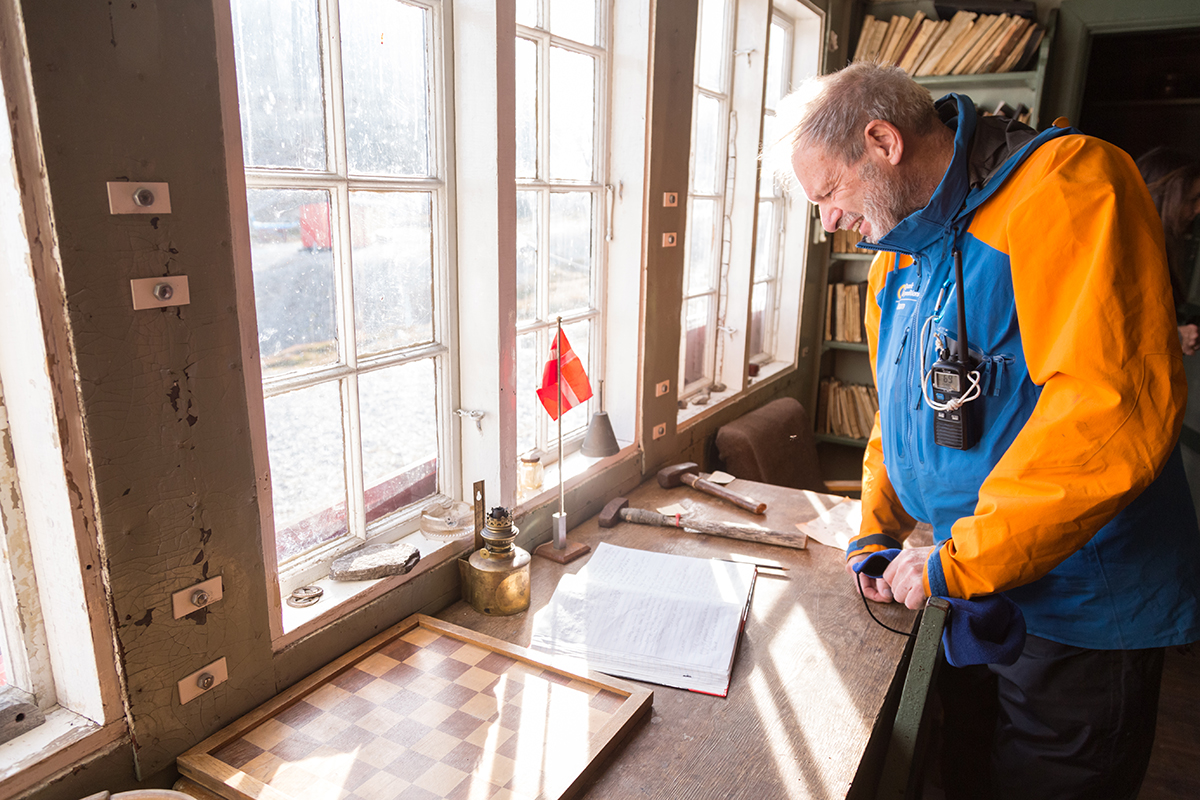 Geologist and expedition guide Michael Hambrey reads through the logbook of the historic hut at Ella Island. Photo by Acacia Johnson