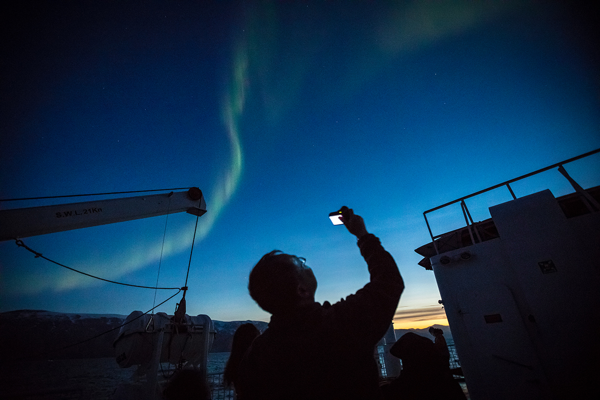 A Quark Expeditions passenger photographs the aurora from the top deck of the ship. Photo by Acacia Johnson