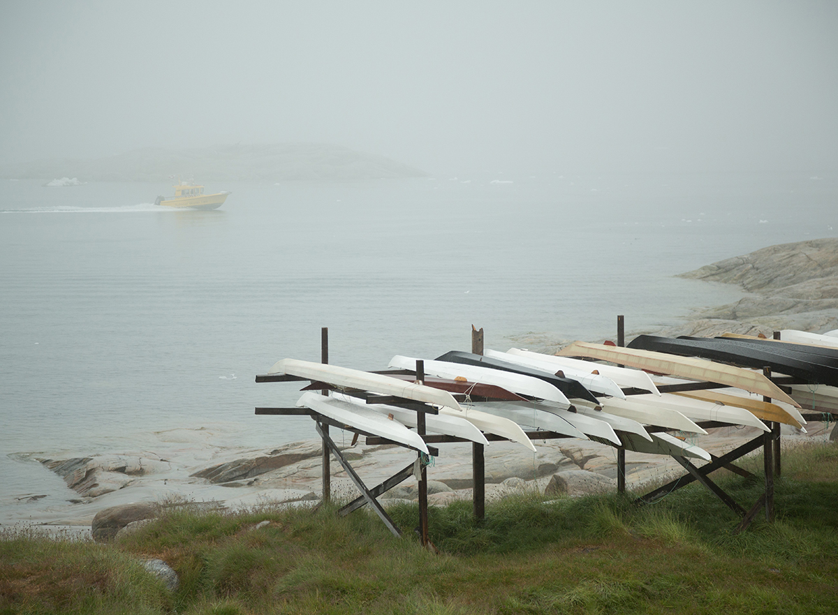 Custom made traditional Greenlandic kayaks sit on top of a rack. Photo by Acacia Johnson