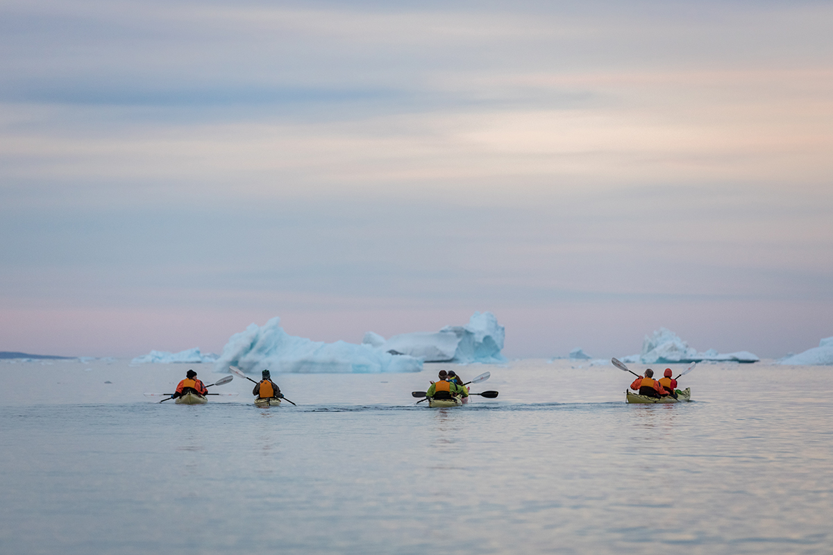 Passengers in the Sea Kayak Program paddle into the sunset in Fønfjord, East Greenland.