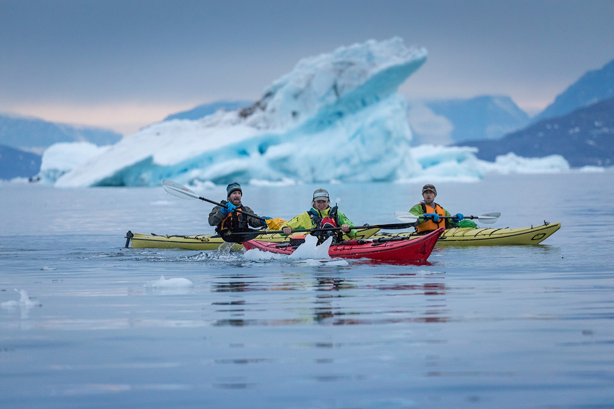 Kayakers paddling through sea ice in the evening. Photo by Acacia Johnson