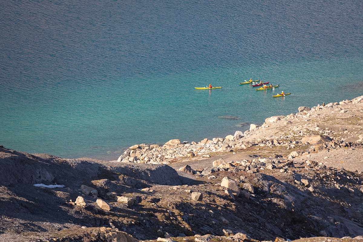 Sea Kayakers traverse the vibrant coast of Skipperdal, East Greenland. Photo by Acacia Johnson