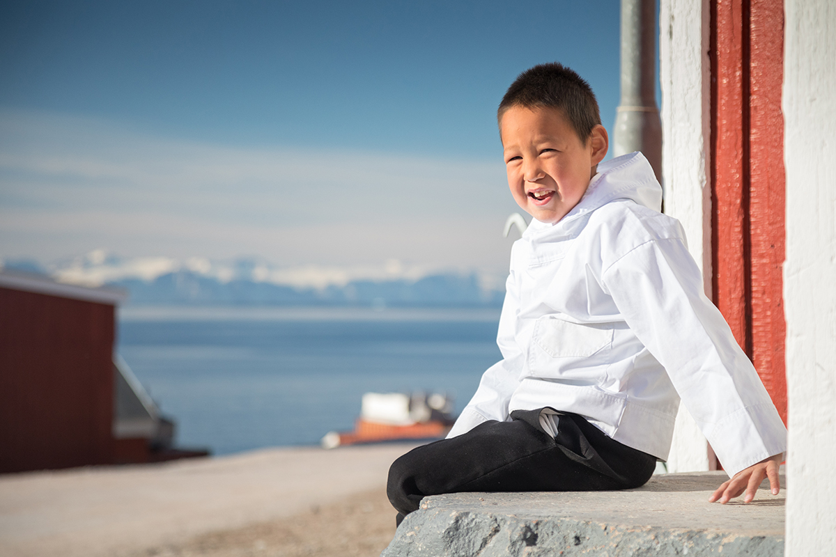 A young Greenlandic boy models the Greenlandic national costume in Ittoqqortoormiit. Photo by Acacia Johnson