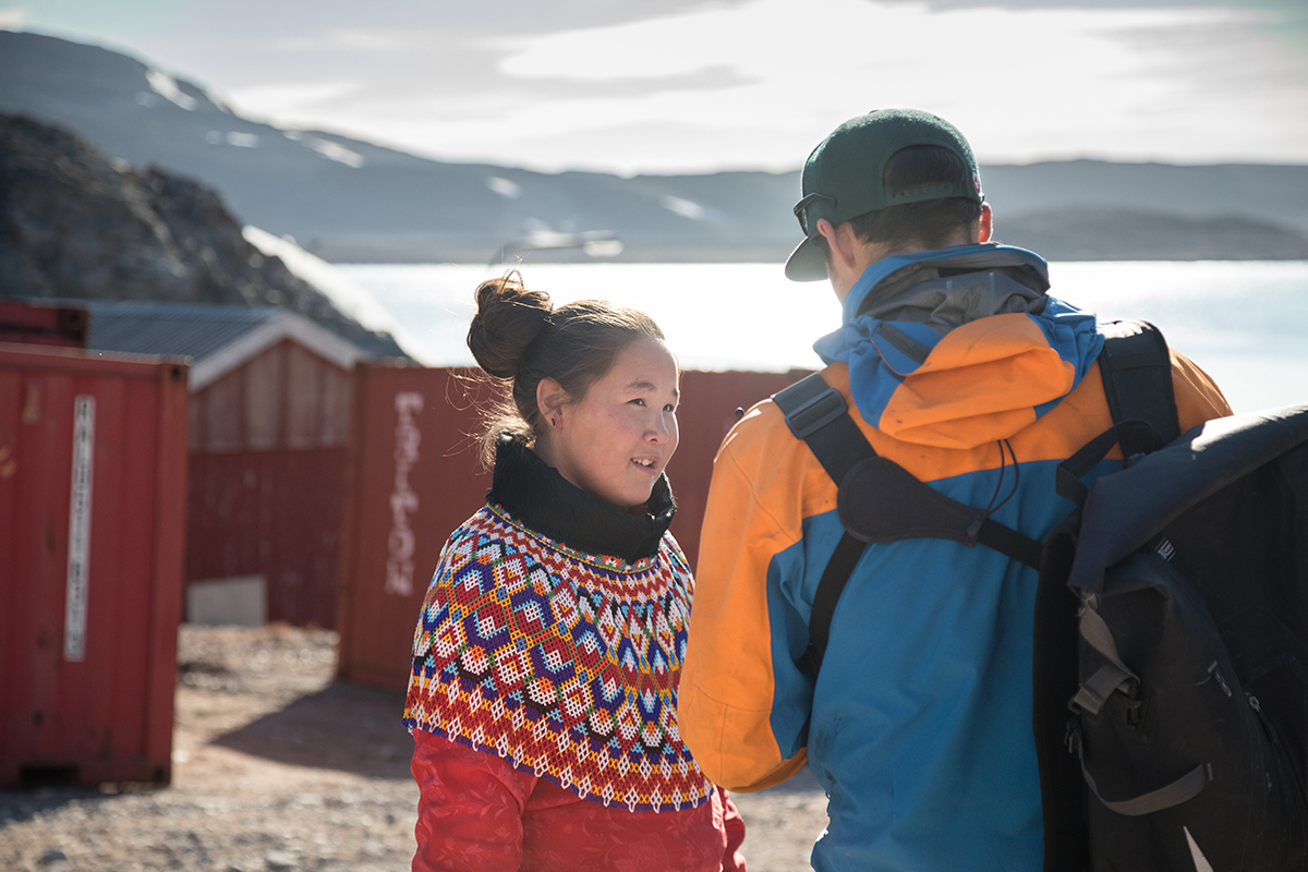 Bella Brandt, wearing the Greenlandic national costume, catches up with Quark Expeditions guide Lauritz Schönfeld in Ittoqqortoormiit. Photo by Acacia Johnson