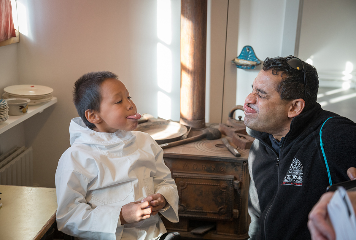Quark Expeditions passenger interacts with a Greenlandic boy. Photo by Acacia Johnson