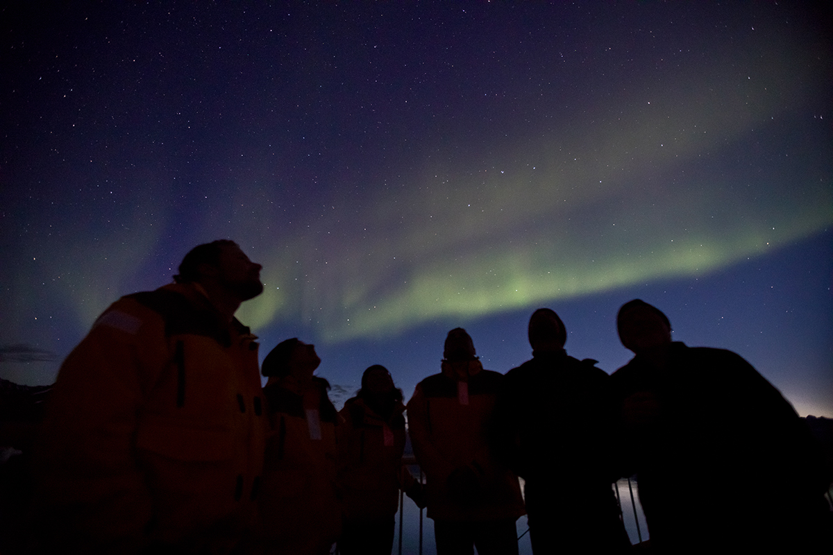 Quark Expeditions Passengers admire the northern lights from the deck of the ship. Photo by Acacia Johnson
