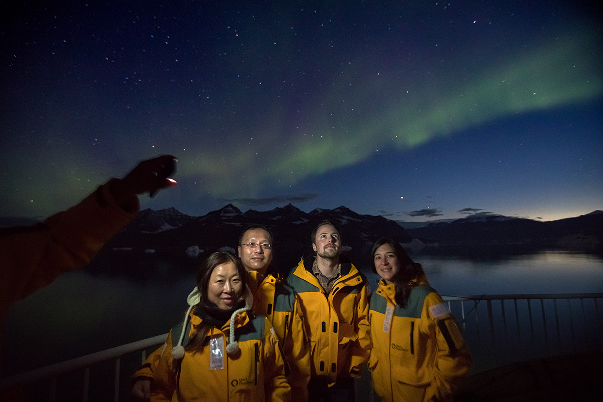 A group photo with the Northern Lights in the background. Photo by Acacia Johnson