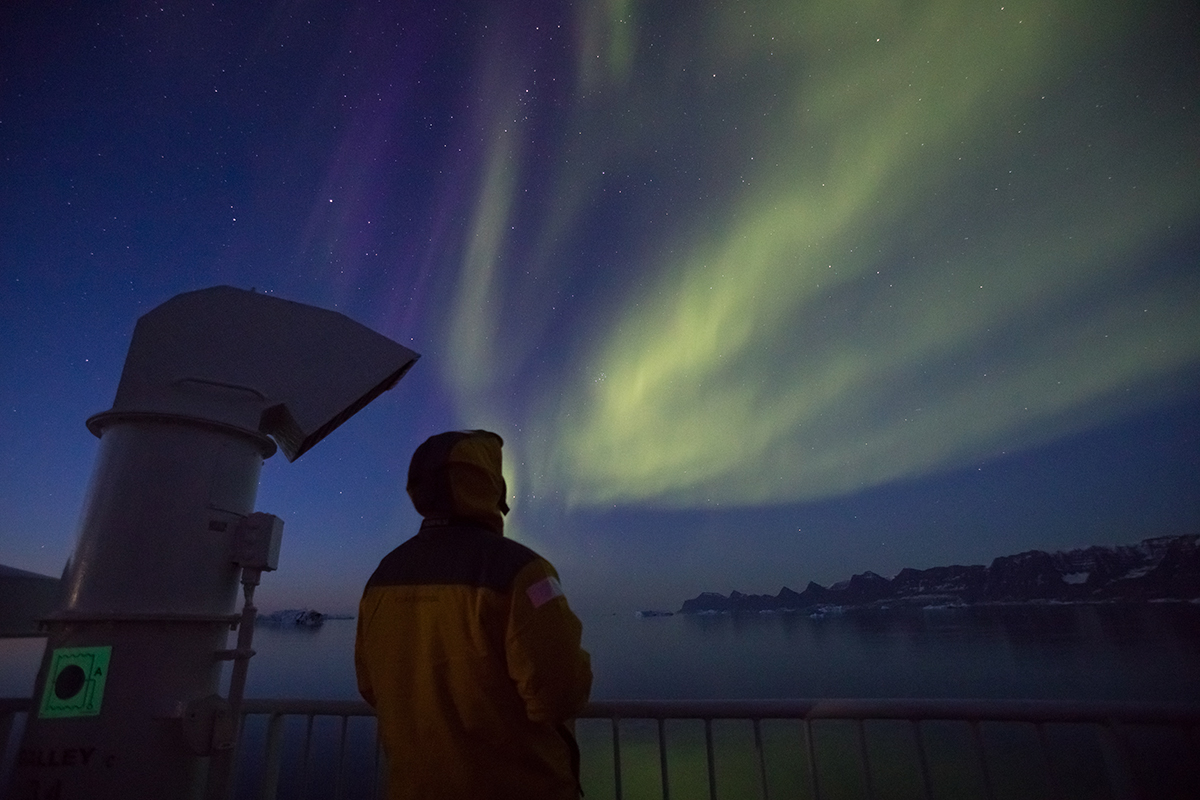 Quark passenger looks into the night sky as the auroras take over. Photo: Acacia Johnson