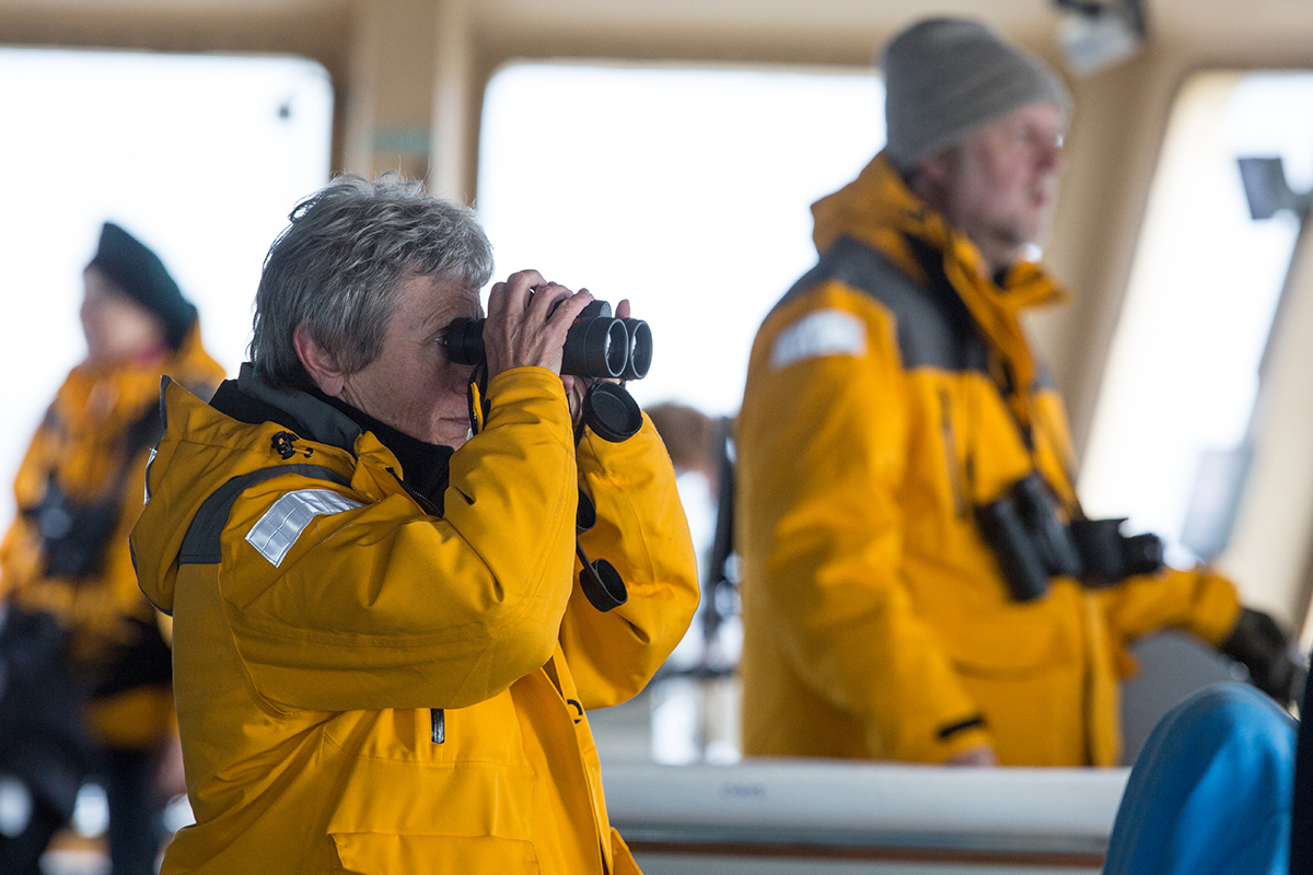 A passenger in a yellow Quark jacket uses binoculars to look out the window on the hull of a ship.