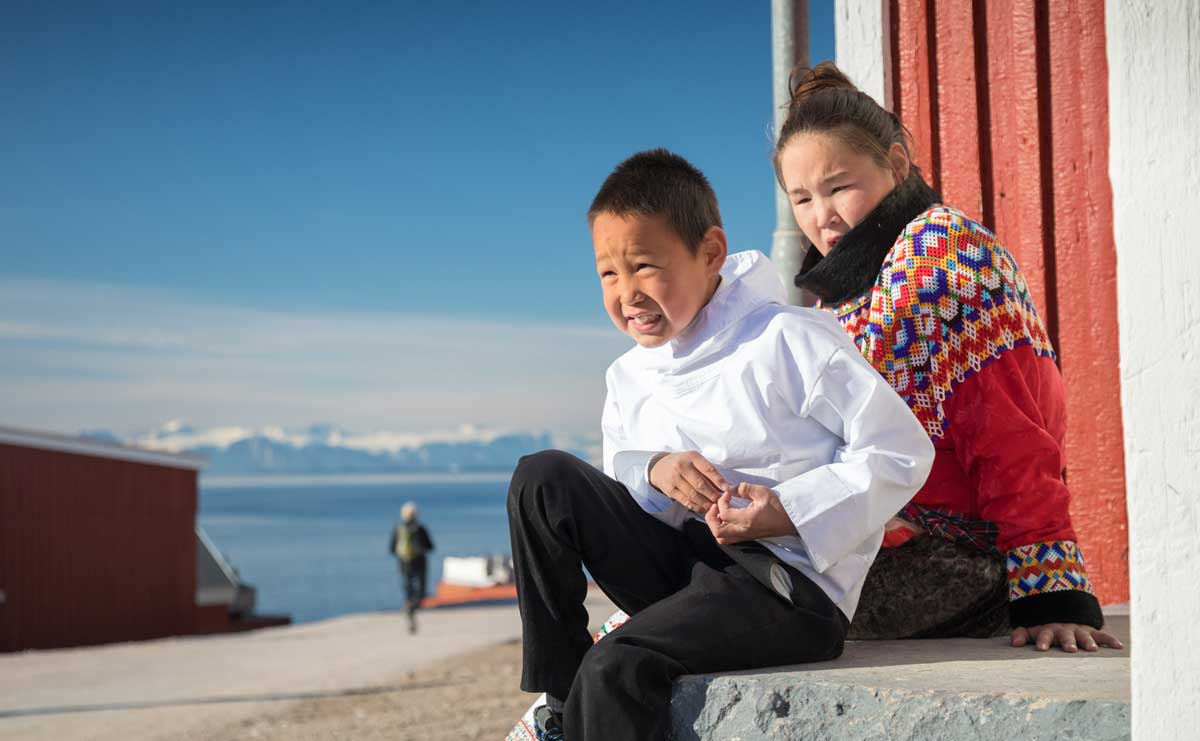 Children sitting on a stoop in an arctic community enjoy the sun.