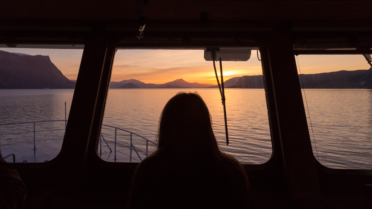 Silhouette of a woman looking across the bow of the ship towards a sunset horizon.