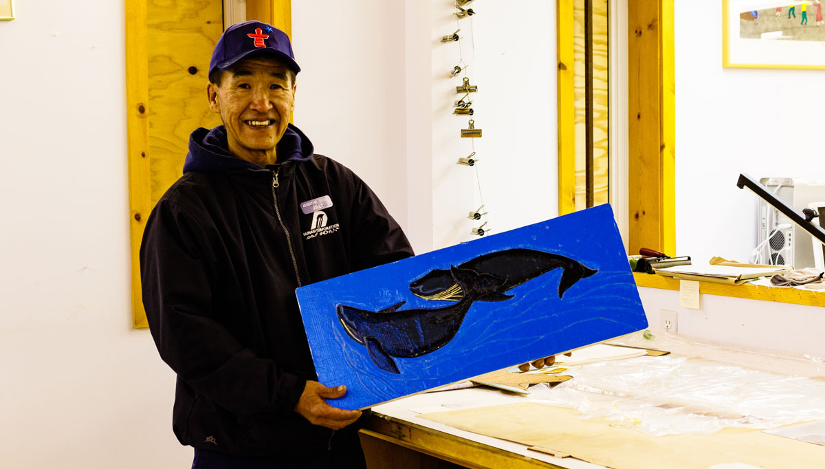 A man holds a painting of two whales.