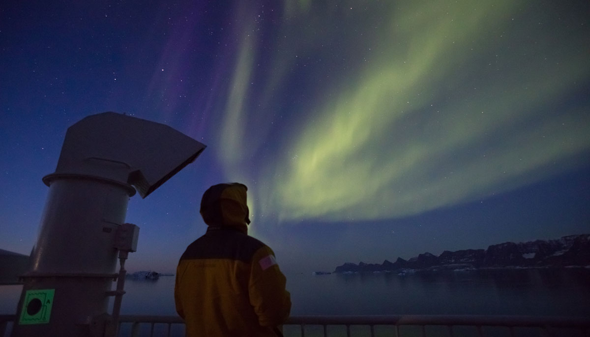 Man in a yellow jacket looks up at the streaks of Northern Lights.