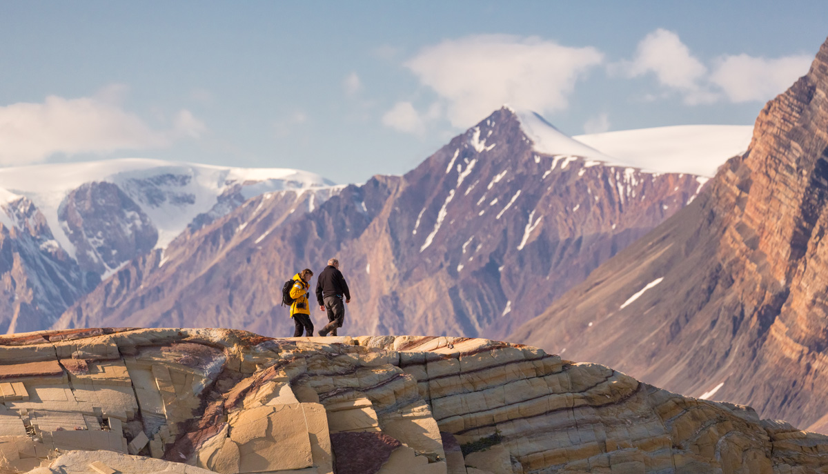 A man and woman walks across a hill with snow-capped mountains in the background.
