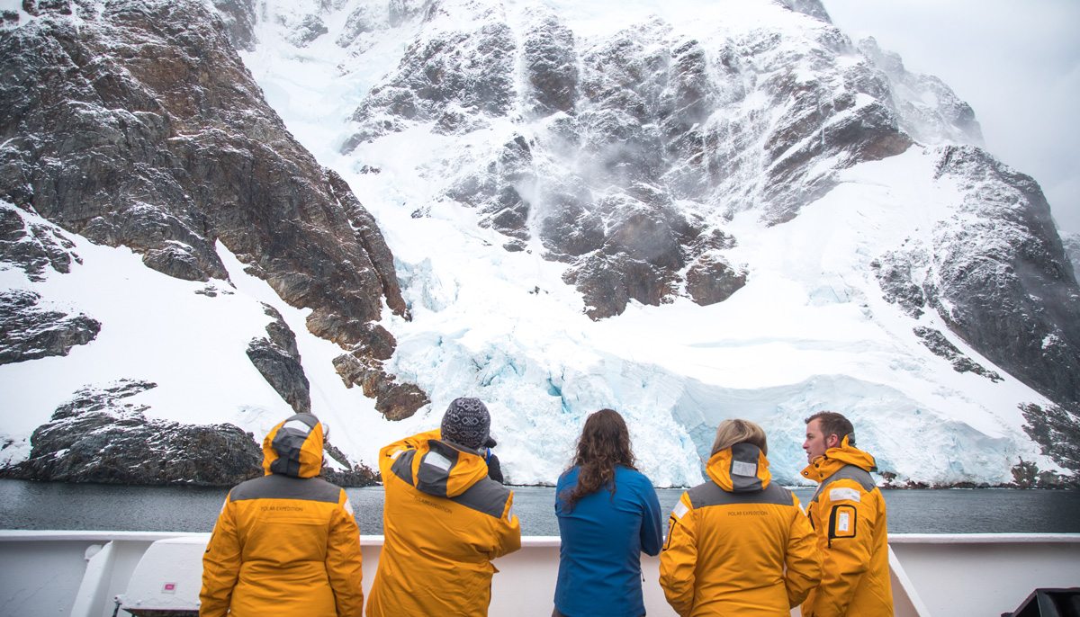 Passengers in yellow jackets stand on a ship and look up at ice covered hills.