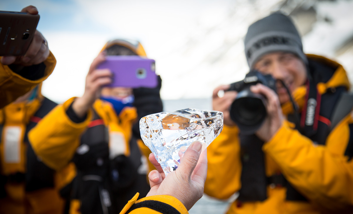 A group of tellow jackets snap a picture of ice held by their guide.