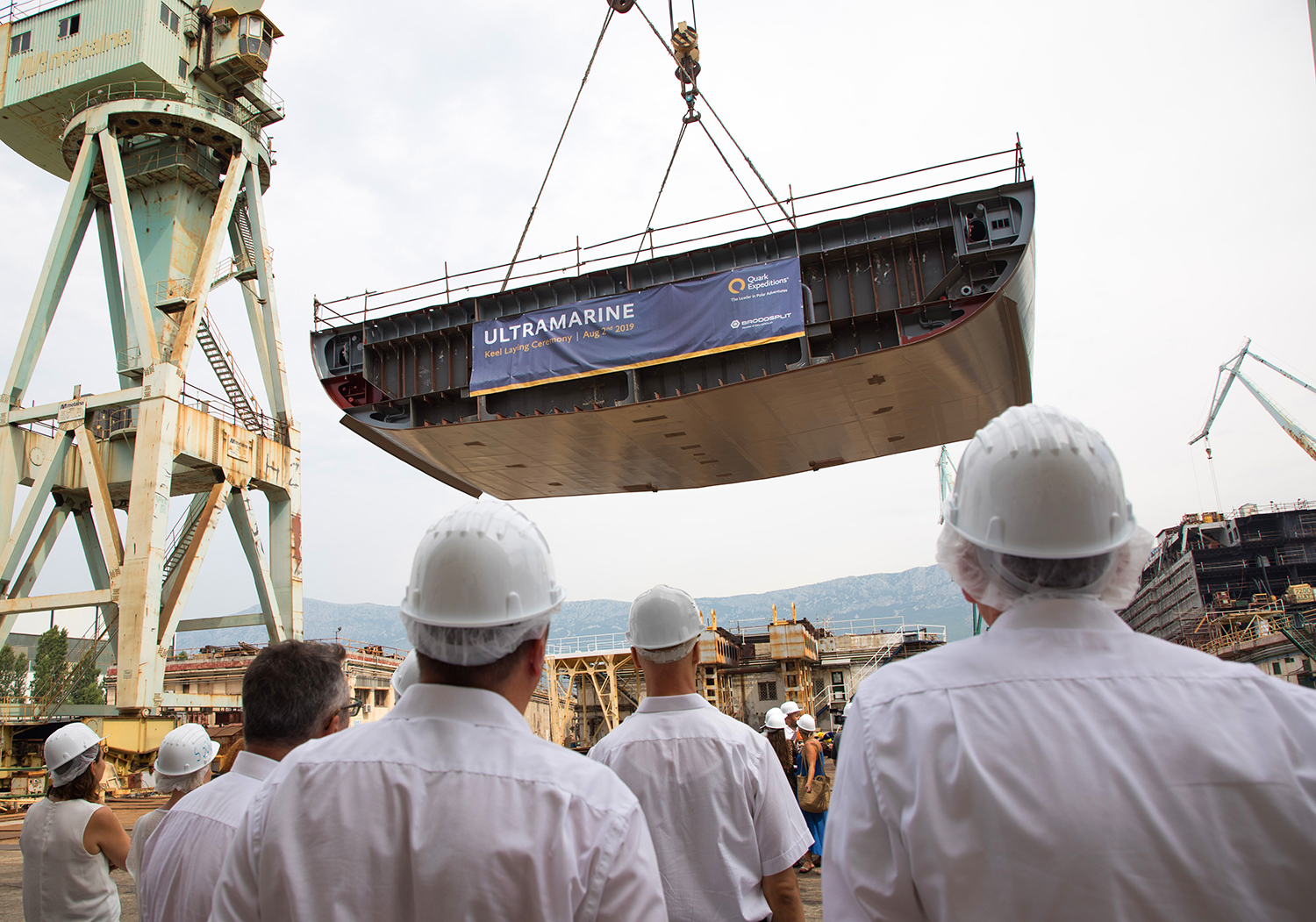Invited guests watch as the keel of Ultramarine is lowered into place for the ceremony