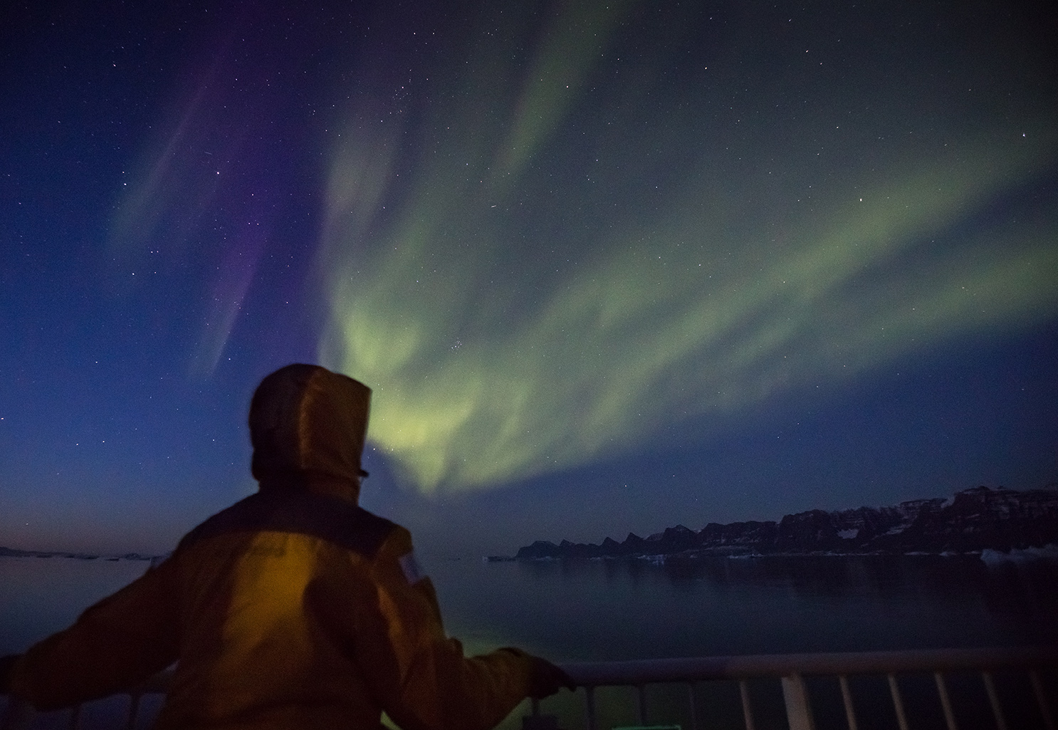 A Quark Expeditions guests witnesses the Aurora borealis from the deck of a polar ship