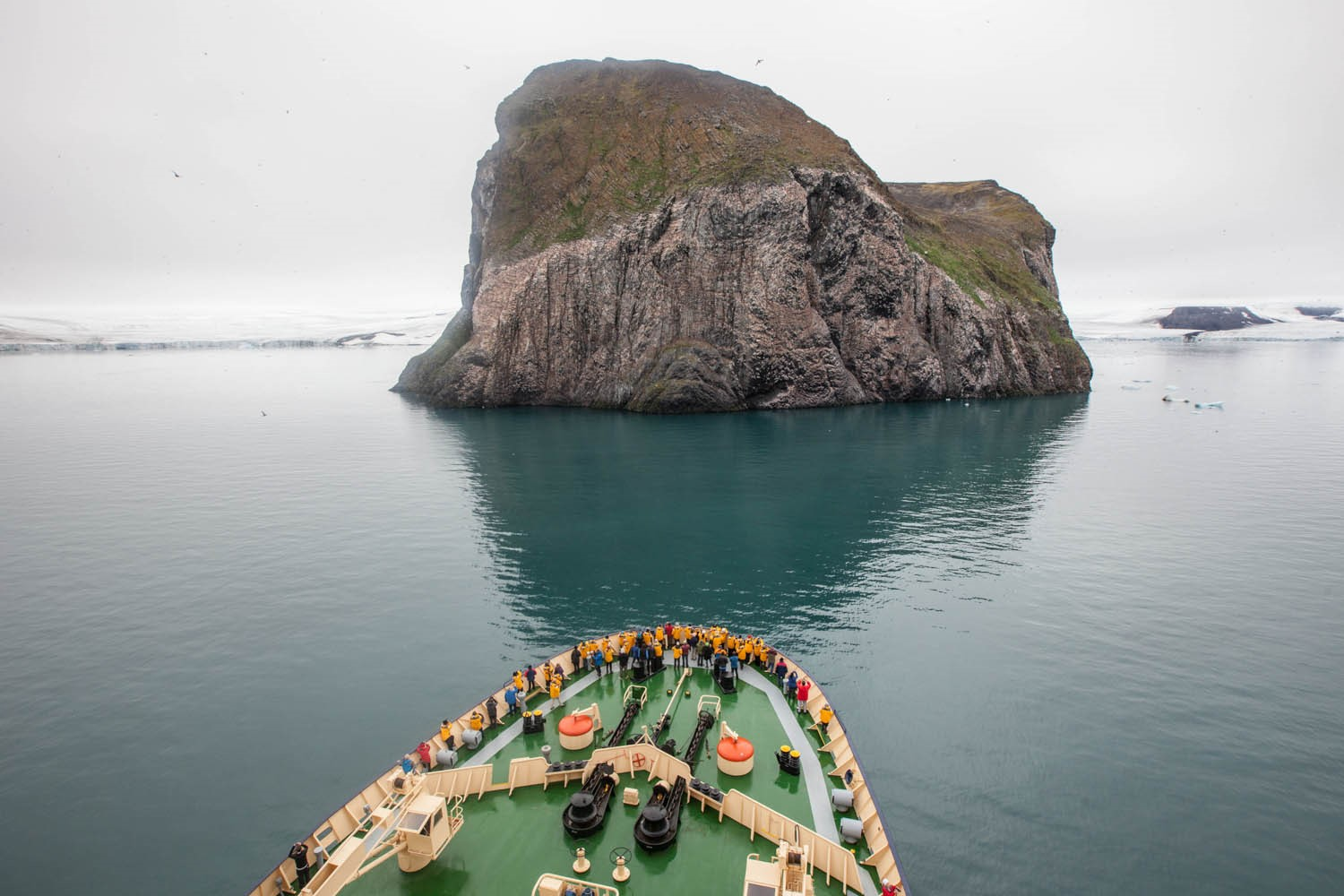 Guests traveling with Quark Expeditions guests on the deck of the ship on a voyage through the remote regions of the Russian Arctic, Franz Josef Land.