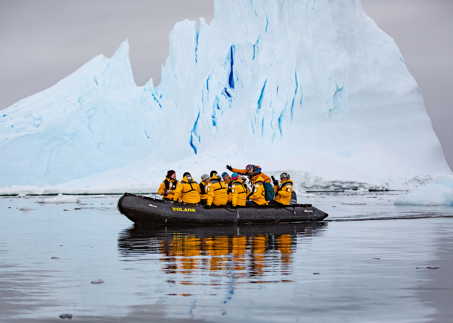 Guests of Quark Expeditions enjoy a close-up view (within a safe distance) of an iceberg while on a Zodiac cruise. Such ice formations can be seen in various parts of Iceland and Greenland.