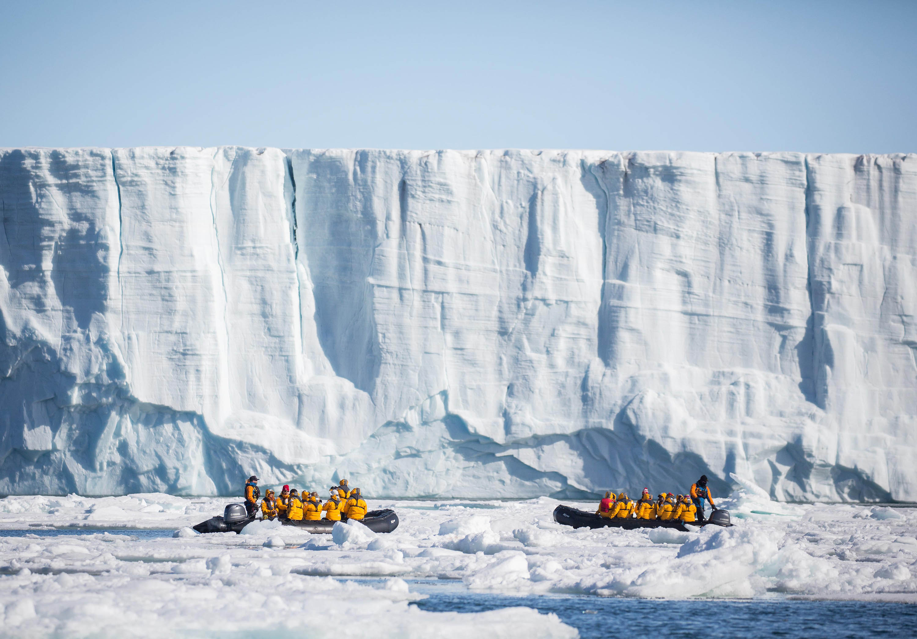 Quark Expeditions guests enjoy a Zodiac cruise in waters of Svalbard