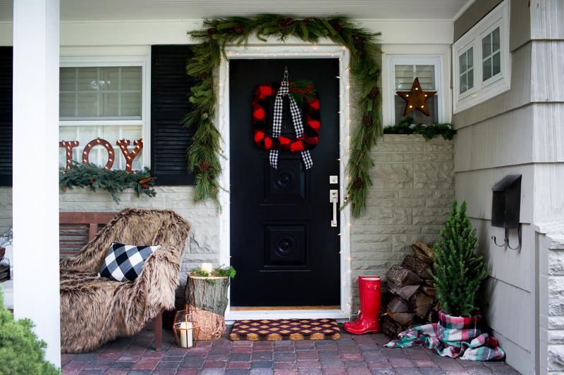 La porte d'entrée d'une maison ornée d'une couronne, de guirlandes et d'autres décorations des fêtes.