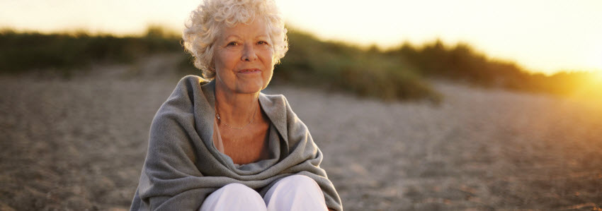 Healthy retired woman sitting on beach, wrapped in blanket
