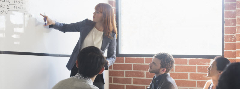 Woman pointing at whiteboard while employees look on