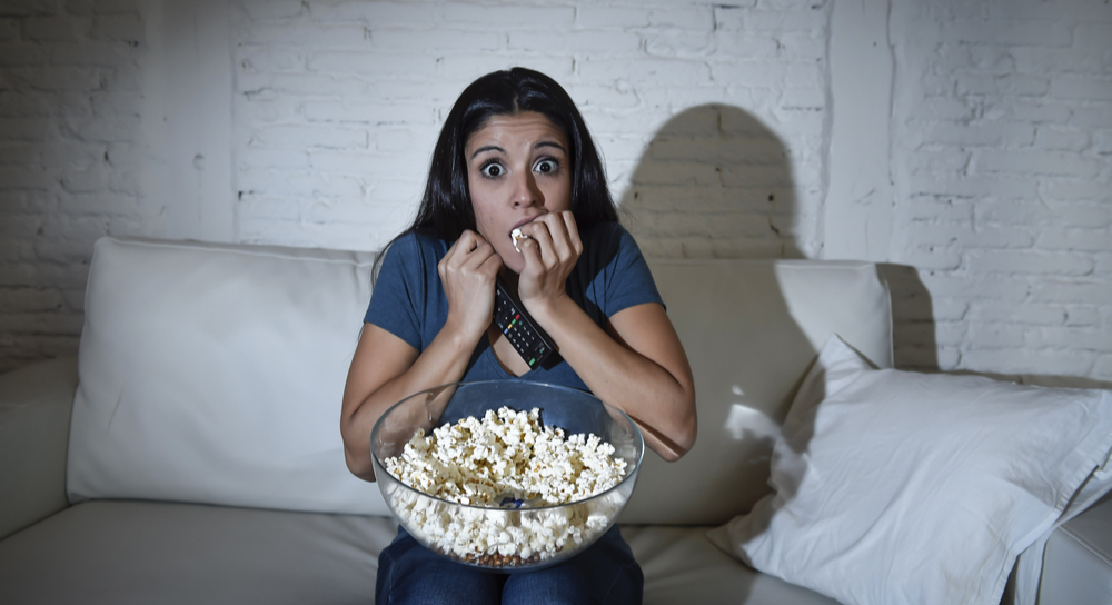 Young woman at home on couch watching television in suspense