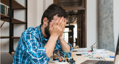 Man with elbows on office desk frustrated over electronics.