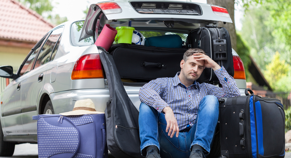 Picture of exhausted man sitting behind his car trying to pack suitcases into it