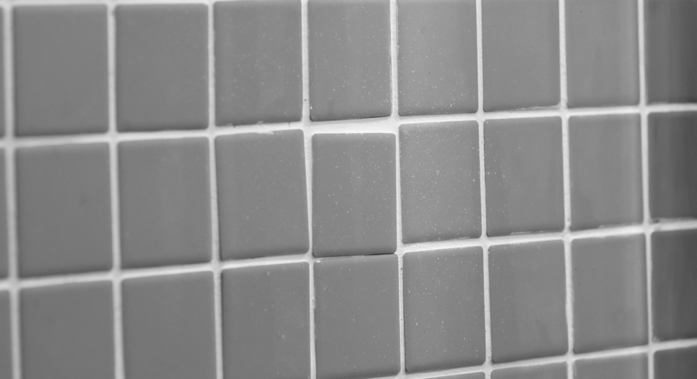 Picture of tiles on a wall with one tile out of place