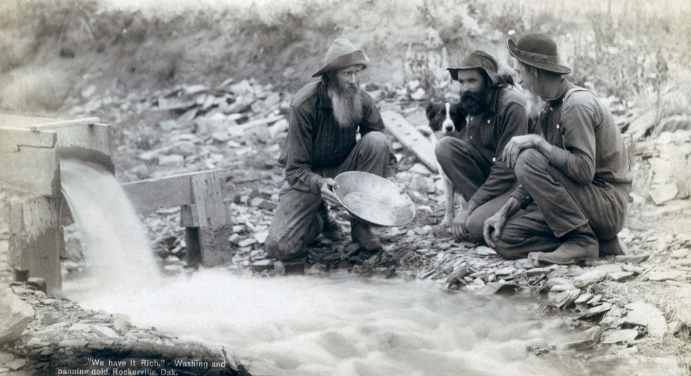 Three men, with dog, panning for gold in a stream in the Black Hills of South Dakota in 1889