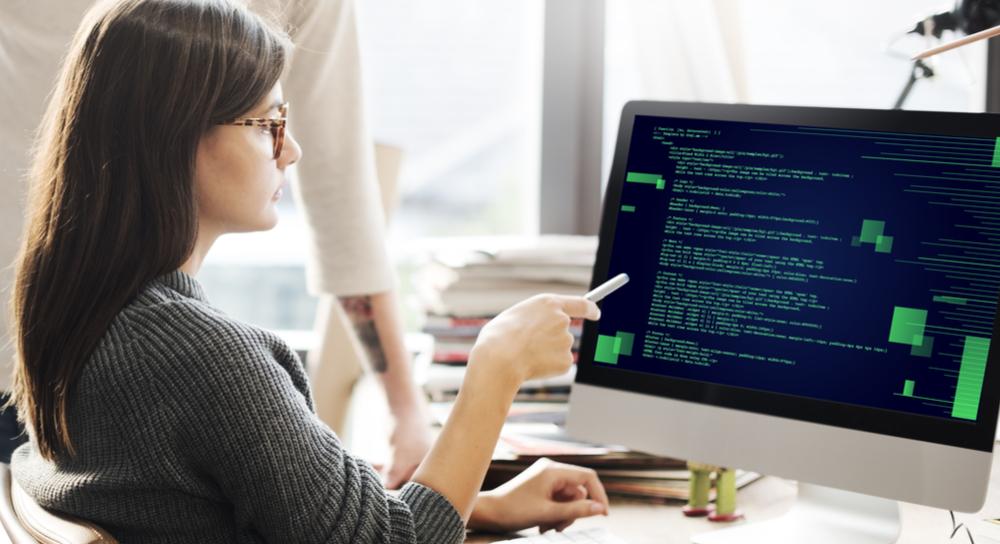 パソコンの画面上のコードをペンで指している女性