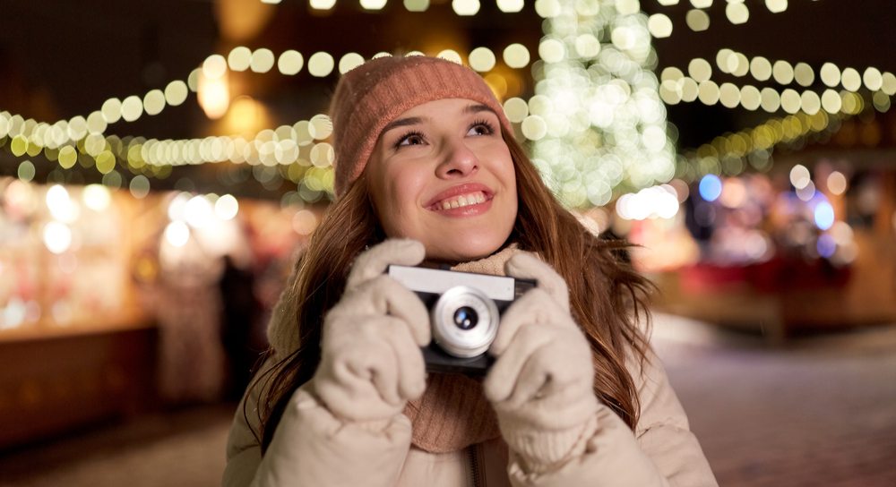 Young women taking pictures of holiday lights