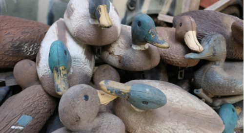 Pile of duck decoys on top of each other.
