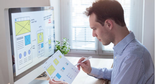 Man matching design on computer screen to design on paper