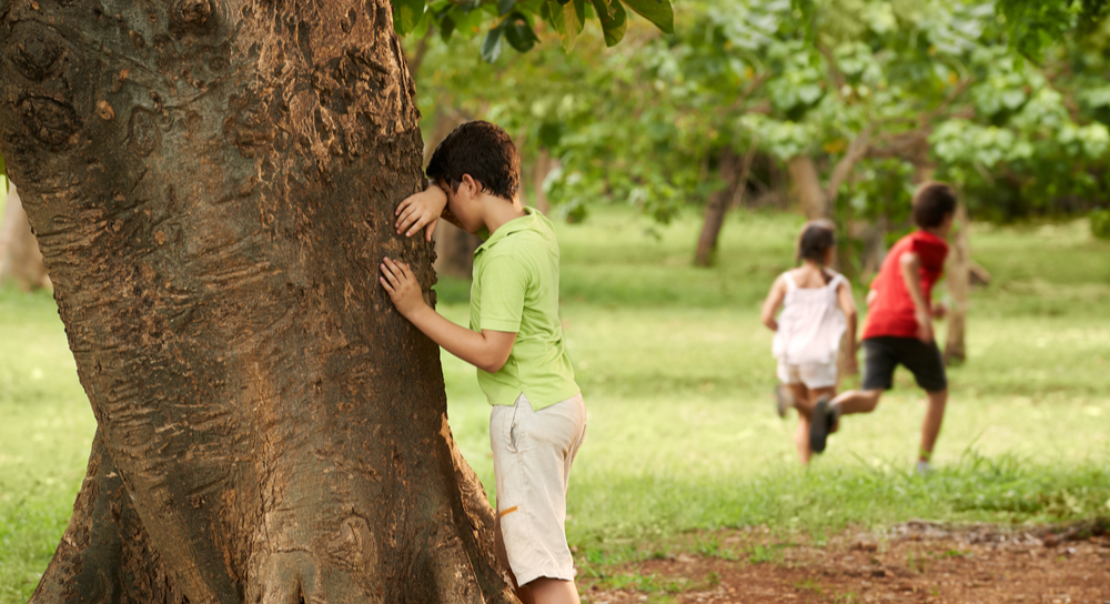 Boy leans against tree while other children run off in grass