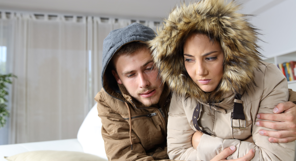 Couple in house dressed warmly because it's cold inside