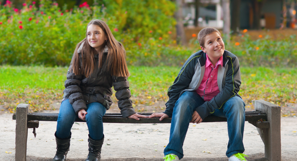 Shy boy and girl on park bench