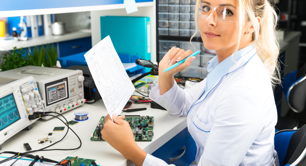 Engineer testing circuit board to schematic