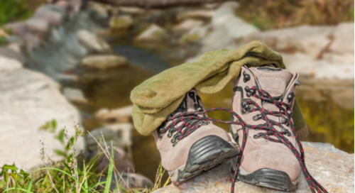 Hiking boots and socks on a boulder.