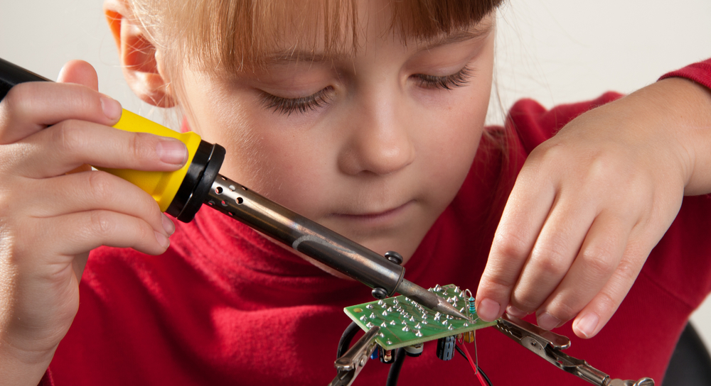 A girl soldering through-hole components onto a PCB.