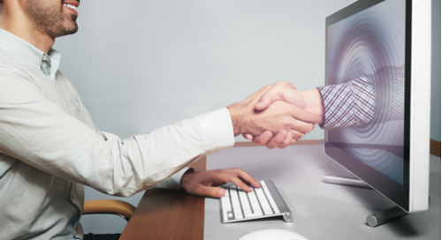 Shaking hands with hand coming out of computer screen