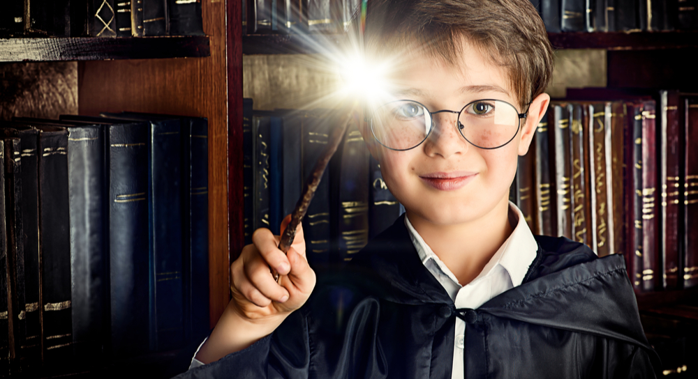Boy with magic wand in library