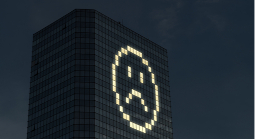 Building with lighted windows in the shape of a frowning face